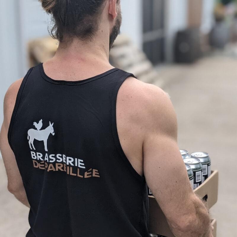 Homme de dos portant une camisole noir et transportant des caisses de bière.
